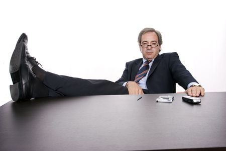 Successfull businessman relaxing over his desk, isolated in white background Stock Photo