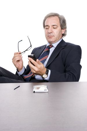 Mature businessman dialing a number in cellphone, over white background photo