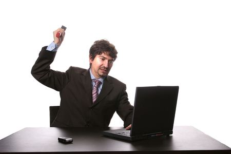 Fustrated businessman in his office threatening to destroy his PC with a hammer out of sheer frustration photo