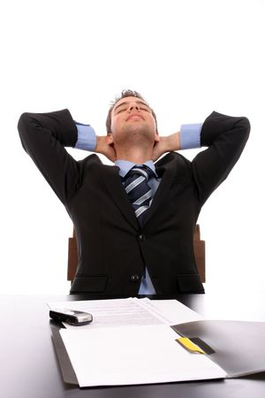 Successfull businessman relaxing over his desk, isolated in white photo