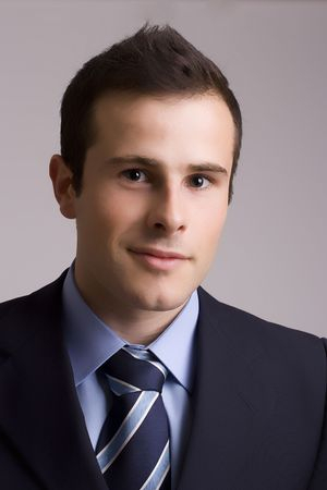 Portrait of young businessman - isolated in grey background photo