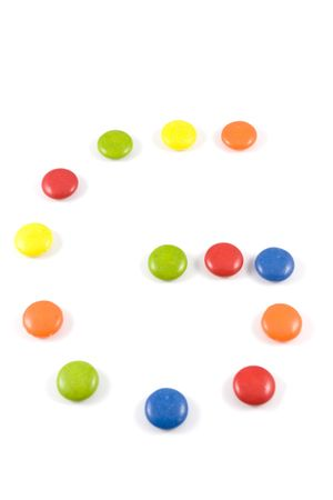 smarties: Letter G made of colored smarties, isolated over white