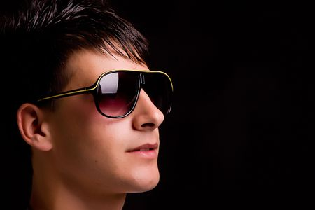 Young boy with sunglasses - low key portrait photo