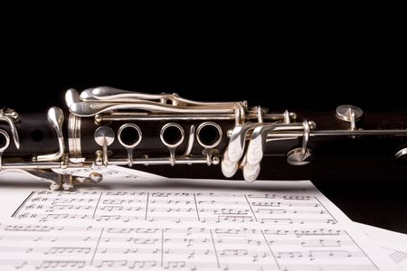 timbre: Photograph of a clarinet isolated over sheet music