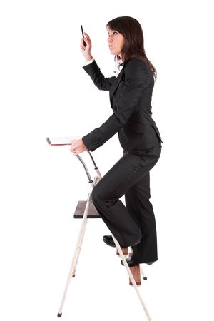 Business woman climbing ladder, isolated over white photo