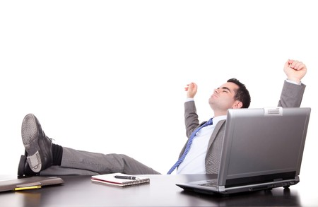 Successful businessman relaxing over desk, isolated photo