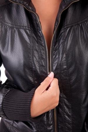 Detail of woman unzipping black coat photo