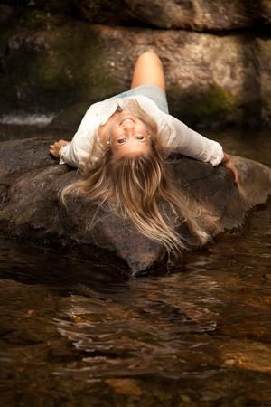 Beautiful woman posing near a waterfall photo