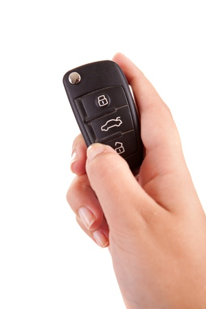 Woman with car key, isolated over white background photo