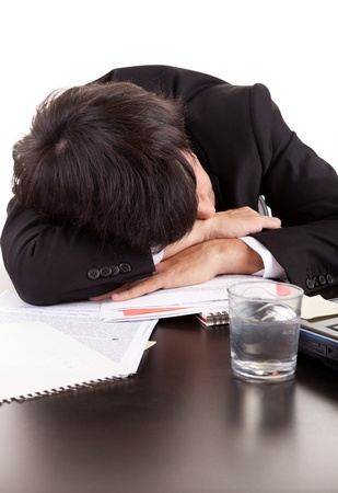 Business man sleeping over the desk, isolated over white photo