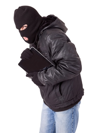 Thief holding a laptop, isolated over white background photo
