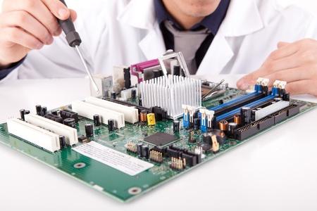 repair man: Computer engineer working on an old motherboard
