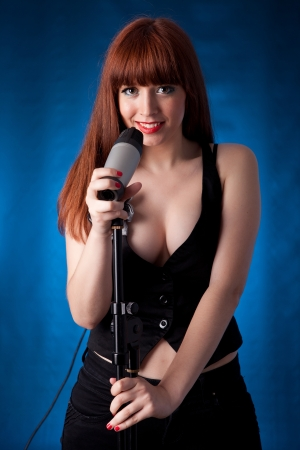 Young and hot singer with microphone photo