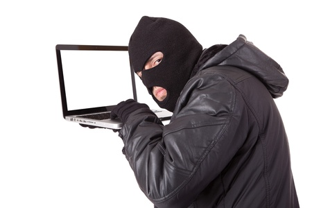 internet crime: Disguised computer hacker with laptop