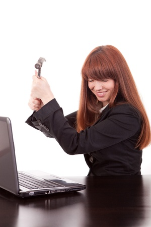 Fustrated businessman in her office threatening to destroy her PC with a hammer out of sheer frustration photo
