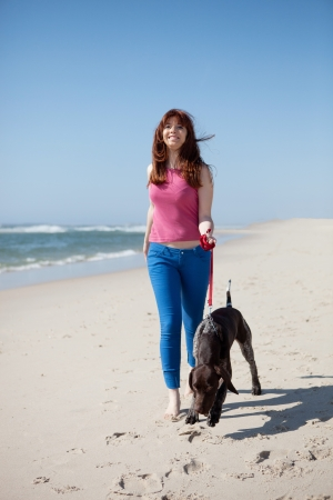 Beautiful young woman at the beach with a dog photo