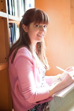 Young woman studying at the library photo