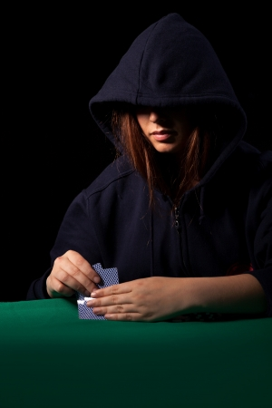 Very beautiful woman playing texas holdem poker - Low key setup for dramatic ambience