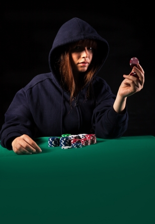 Very beautiful woman playing texas holdem poker - Low key setup for dramatic ambience photo