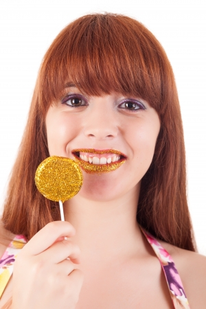 Beautiful woman eating a lollipop, over white background photo