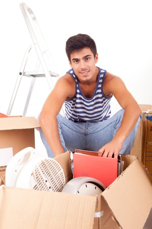Young man moving to new house, isolated over white photo