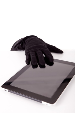 A thief stealing a tablet computer - piracy concept photo