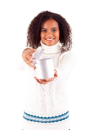 Happy young woman holding a gift, isolated over white photo