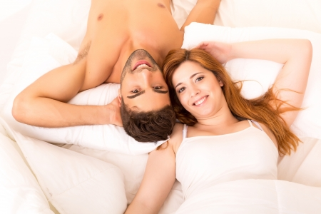 A beautiful young passionate couple in bed photo