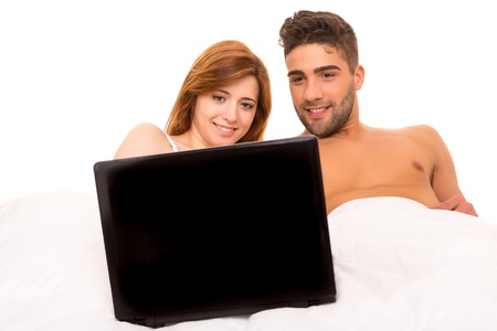 Happy couple watching a movie in bed photo