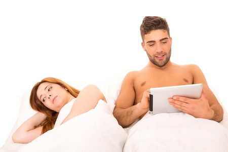 Couple in bed - mans watching something on his computer and woman doesnt like it photo