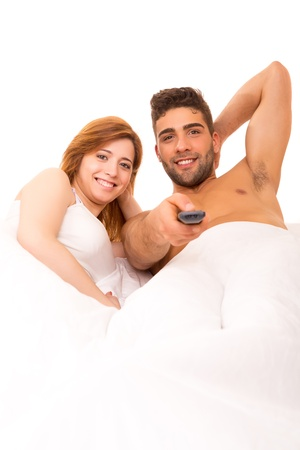 Happy couple watching television in bed photo