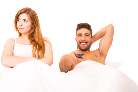 Couple in bed - Man is watching television and woman doesn't like it photo