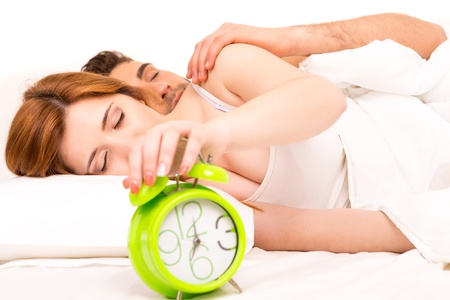 Couple is sleeping and the alarm clock starts to ring - time to wake up! photo