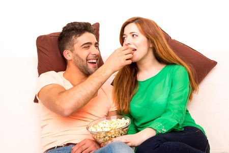 appearance: Young couple watching something on the television in the couch