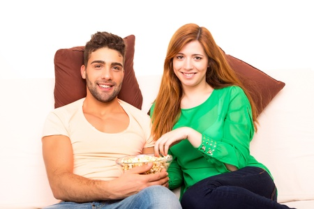 Young couple watching something on the television in the couch photo