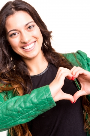 Beautiful woman making a heart shape with her hands, isolated over white background photo