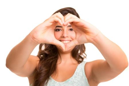 corazon en la mano: Hermosa mujer haciendo una forma de coraz�n con sus manos, aisladas sobre fondo blanco Foto de archivo