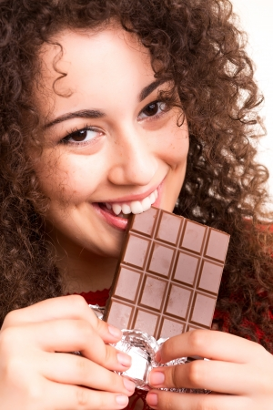 Beautiful young woman eating a chocolate bar photo