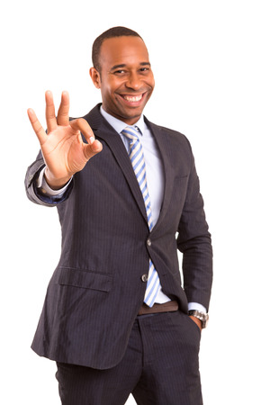 Handsome young african business man signaling ok, isolated over white photo