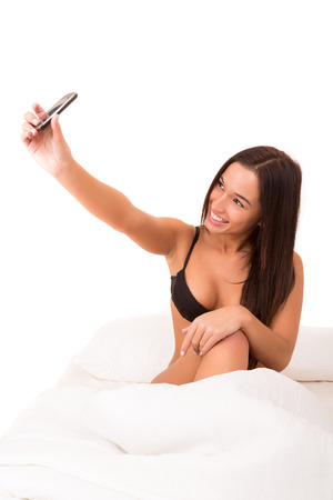 Beautiful asian woman making a self portrait in bed with her cellphone photo