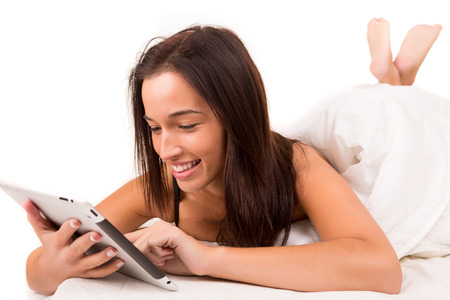 Happy asian woman in bed working with a tablet computer photo