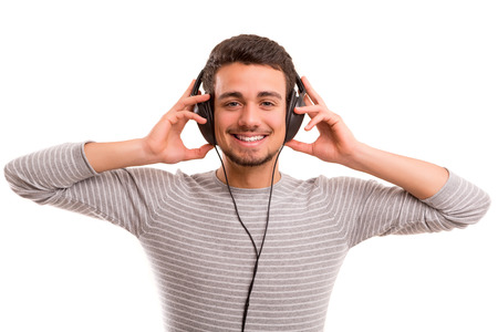 Happy young man with headphones on and listening to music Stock Photo