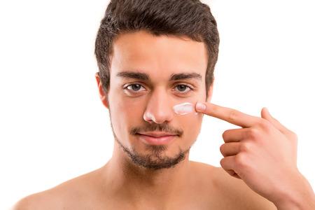 belleza masculina: Hombre hermoso que aplica - concepto anti-envejecimiento