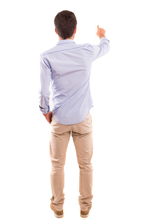 A young man with his back turned to camera, pointing to something