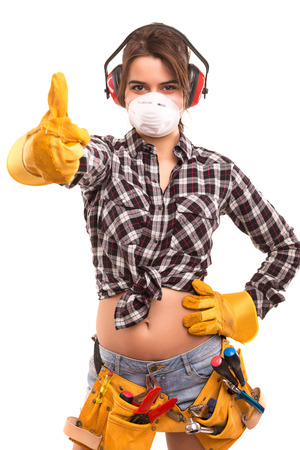 Sexy young woman construction worker signaling ok photo