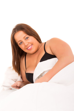 Beautiful large woman relaxing on her bed photo