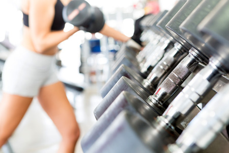 weight training: A young and beautiful woman working out at the gym