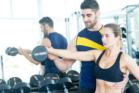 aide � la personne: Belle jeune femme travaillant � la gym avec l'aide de son entra�neur personnel
