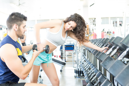 Beautiful young woman working out at the gym with the help of her personal trainer photo