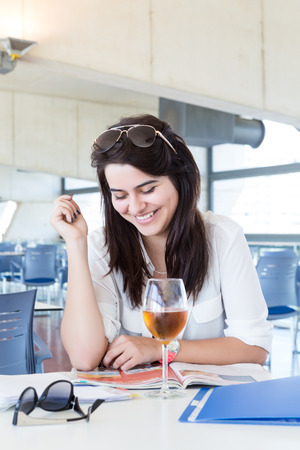 Happy student preparing her exams or simply relaxing at a bar photo